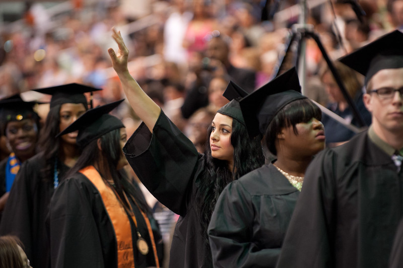 Buff State graduate waving in the crowd