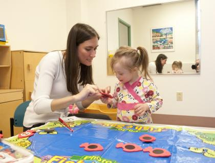 Speech-Language-Pathology Graduate Student conducting speech therapy with a child