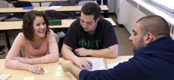 Three students working on a group project in a business class