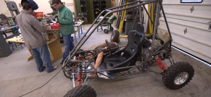 Mechanical engineering students work on a mini baja car